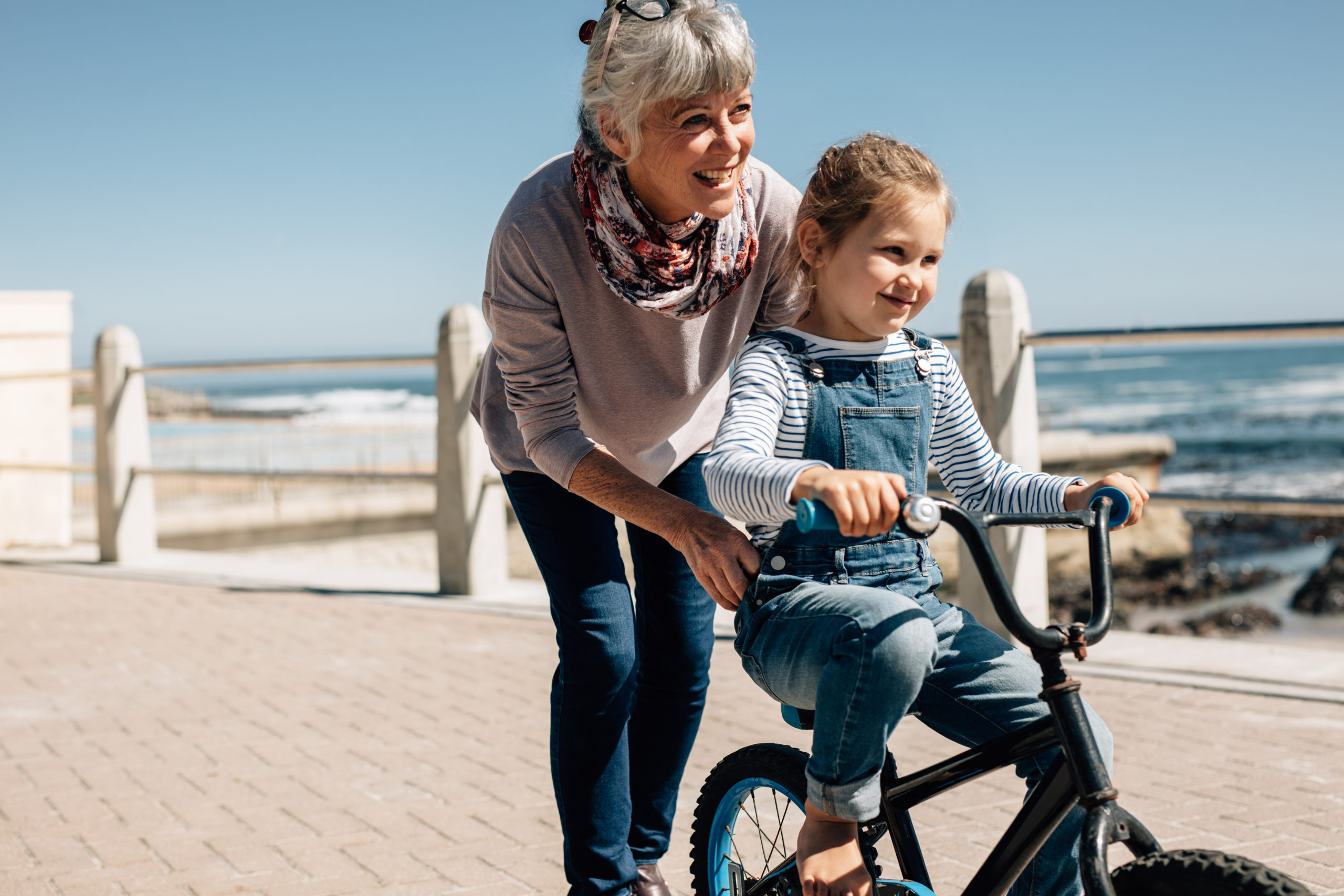 Girl trying to ride a bicycle with the help of her grandmother at seaside promenade. Senior woman holding the bicycle while her granddaughter learns to ride it.